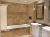 Master Ensuite - purpose made shelving unit at end of bath, marble tops and bath surround with tile TV